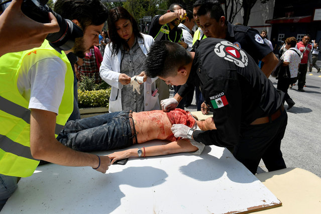 A woman is assisted after being injured during a quake in Mexico City on September 19, 2017. A powerful earthquake shook Mexico City on Tuesday, causing panic among the megalopolis' 20 million inhabitants on the 32nd anniversary of a devastating 1985 quake. The US Geological Survey put the quake's magnitude at 7.1 while Mexico's Seismological Institute said it measured 6.8 on its scale. The institute said the quake's epicenter was seven kilometers west of Chiautla de Tapia, in the neighboring state of Puebla. (Photo by Omar Torres/AFP Photo)