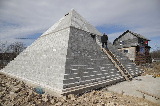 Andrey Vakhrushev stands at the entrance to his pyramid built on the grounds of his rural house in Istinka village, outside St. Petersburg, Russia, Wednesday, March 25, 2020. Andrey and his wife Victoria built this 9 meters high and 400 tons weigh pyramid as a small copy of the Cheops pyramid in Egypt. (Photo by Dmitri Lovetsky/AP Photo)
