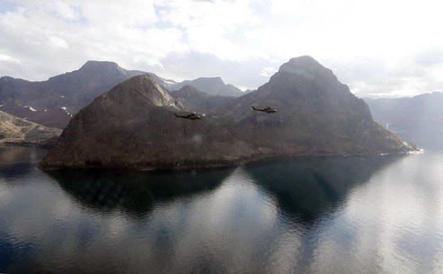 Two Canadian Forces Griffon helicopters fly from York Sound to Iqaluit after taking part in the Operation Nanook military exercise on Baffin Island, Nunavut August 26, 2014. (Photo by Chris Wattie/Reuters)