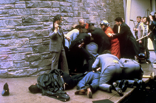 In this March 30, 1981 file photo, a U.S. secret service agent with an automatic weapon watches over James Brady, the president's secretary, after being wounded in an attempt on the life of President Ronald Reagan in Washington. A Washington, D.C. policeman, Thomas Delahanty, lies to the left after also being shot. John Hinckley Jr. shot four people outside a Washington hotel on March 30, 1981, but two of his victims understandably got most of the attention: President Ronald Reagan and his press secretary, James Brady. Former Secret Service agent Timothy McCarthy and former District of Columbia police officer Thomas Delahanty, both of whom took bullets to protect the president. (Photo by Ron Edmonds/AP Photo)