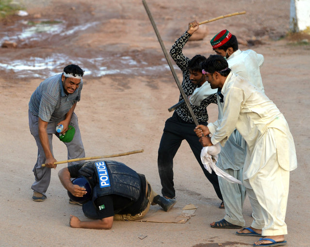 Pakistani supporters of cricketer-turned politician Imran Khan and Canadian cleric Tahir ul Qadri beat a riot policeman during an anti-government protest in Islamabad on September 1, 2014. (Photo by Aamir Qureshi/AFP Photo)