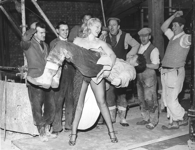 Men, working on the site of Quaglino's new banqueting rooms, look on in amazement as strong-woman Joan Rhodes demonstrates her strength by lifts one of their co-workers. She is appearing in cabaret at Quaglino's restaurant and decided to visit the men working next door. 8th April 1958. (Photo by Reg Speller/Fox Photos)