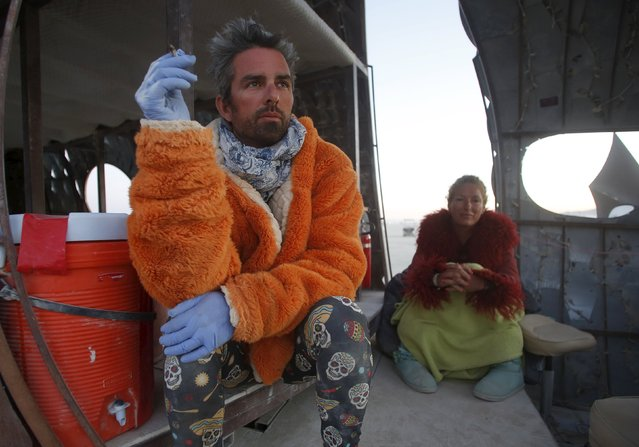 """David McFate (L) and Dixie Johnson wait for the Temple of Promise to burn during the Burning Man 2015 """"Carnival of Mirrors"""" arts and music festival in the Black Rock Desert of Nevada, September 6, 2015. (Photo by Jim Urquhart/Reuters)"""