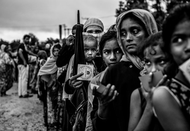 Rohingya refugees line up to get food aid from a local NGO after arriving from Myanmar at the Balukali refugee camp on September 18, 2017 in Cox's Bazar, Bangladesh. (Photo by Kevin Frayer/Getty Images)