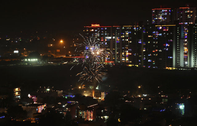 Residential buildings are decorated with colorful lights, as a firecracker lights up, during Diwali festival in New Delhi, India, Thursday, October 19, 2017. (Photo by Altaf Qadri/AP Photo)