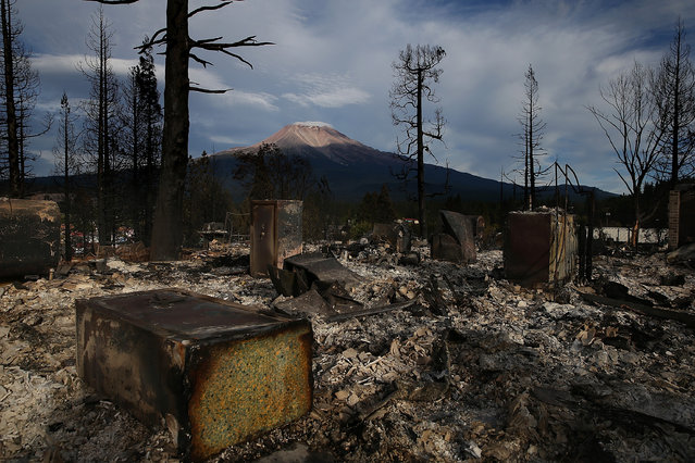 The remains of a home destroyed by the Boles Fire is shown in front of Mount Shasta on September 16, 2014 in Weed, California. Fueled by high winds, a fast-moving wildfire swept through the town of Weed yesterday afternoon, burning 100 structures that included the high school and a lumber mill. (Photo by Justin Sullivan/Getty Images)