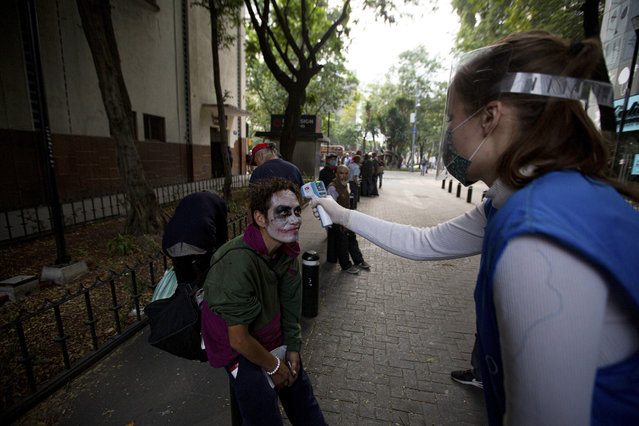 A volunteer takes the temperature of a homeless man with his face painted, screening for COVID-19 symptoms at a line to receive a free meal in Mexico City, Wednesday, May 20, 2020. The volunteers running the soup kitchen say they have had to expand their service from a single day to two days per week as the number of people in need grows. (Photo by Fernando Llano/AP Photo)