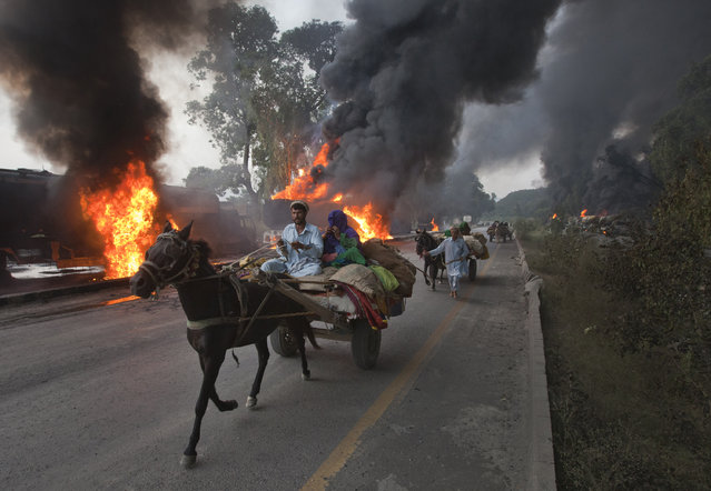 Residents on horse-led carts hurry past burning fuel tankers along the GT Road near Nowshera, located in Pakistan's Khyber-Pakhtunkhwa Province October 7, 2010. Gunmen in Pakistan set fire to up to 40 supply trucks for NATO troops in Afghanistan, police said. (Photo by Adrees Latif/Reuters)