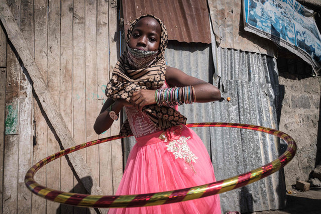 An orphan plays with her new hula hoop during the food and toy distribution, for total about 500 orphans in 11 orphanages, by National Muslim COVID-19 Response Committee to celebrate Eid al-Fitr, the Muslim holiday which marks the end of the fasting month of Ramadan at Good hope markazil Banatil Islamia orphans centre in Nairobi, Kenya, on May 25, 2020. (Photo by Yasuyoshi Chiba/AFP Photo)