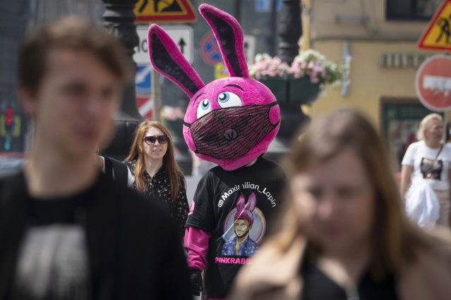 A person dressed as a bunny and wearing a funny face mask advertises a store amid the ongoing COVID-19 pandemic in St. Petersburg, Russia, Wednesday, June 10, 2020. (Photo by Dmitri Lovetsky/AP Photo)