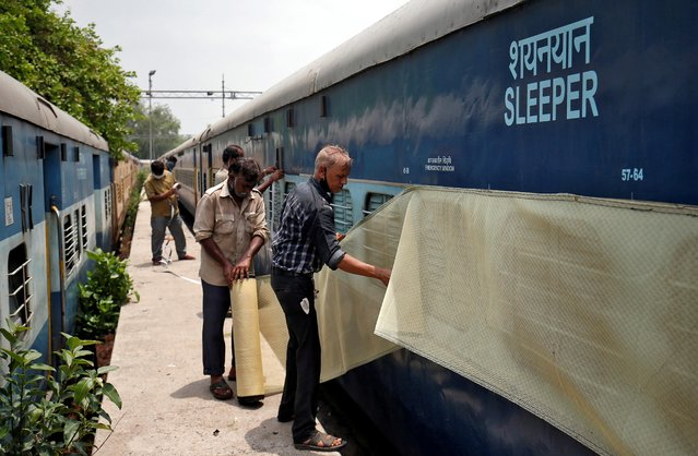 Workers fix mosquito net on a parked passenger train that will be equipped for the care of coronavirus disease (COVID-19) patients amidst the spread of the disease, at a railway yard in Ahmedabad, India, June 16, 2020. (Photo by Amit Dave/Reuters)