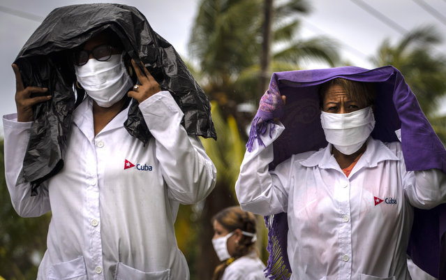 Health professionals who volunteered to travel to Kuwait to treat of coronavirus patients walk in the rain after attending their farewell ceremony in Havana, Cuba, Thursday, June 4, 2020. (Photo by Ramon Espinosa/AP Photo)