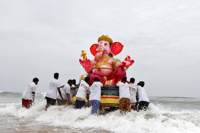 Devotees carry an idol of the Hindu god Ganesh, the deity of prosperity, into the Bay of Bengal for its immersion during the ten-day-long Ganesh Chaturthi festival in Chennai, India, September 20, 2015. During the festival, idols are taken through the streets in a procession accompanied by dancing, singing and later immersed in a river or the sea in accordance with the Hindu faith. (Photo by Reuters/Stringer)