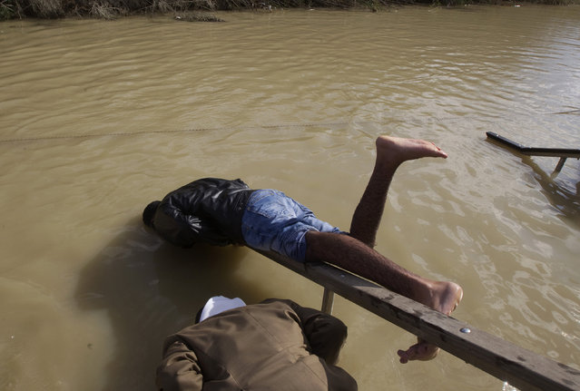 Ethiopian Orthodox Christian pilgrims partially dunk themselves in the Jordan River during a ceremony at the baptismal site known as Qasr el-Yahud, near the West Bank city of Jericho January 19, 2012. (Photo by Ronen Zvulun/Reuters)
