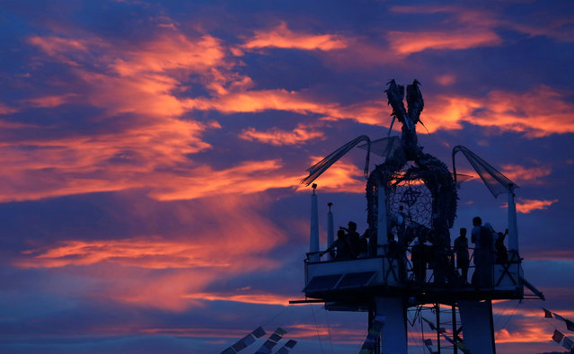 Participants watch the sunset from the Tower of Ascension as approximately 70,000 people from all over the world gather for the 30th annual Burning Man arts and music festival in the Black Rock Desert of Nevada, U.S. August 29, 2016. (Photo by Jim Urquhart/Reuters)