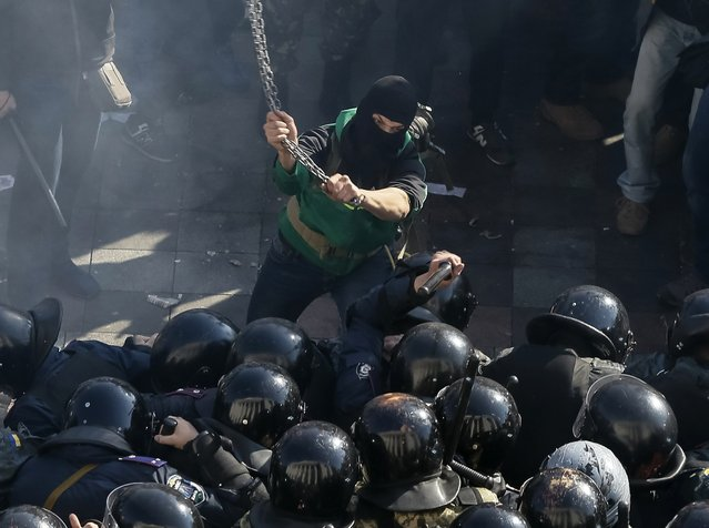 A radical protester clashes with law enforcement members on the Day of Ukrainian Cossacks, marked by activists and supporters of the All-Ukrainian Union Svoboda (Freedom) Party and far-right activists and nationalists to honour the role of the movement in the history of Ukraine, during a rally near the parliament building in Kiev, October 14, 2014. The radical protesters demanded the release of political prisoners in Ukraine. (Photo by Gleb Garanich/Reuters)