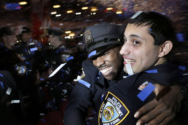 New police officers hug and celebrate amidst confetti during their graduation ceremony at the Beacon Theatre in New York, Thursday, December 28, 2017. The new recruits will join approximately 36,000 other police officers on the largest police force in the United States. (Photo by Seth Wenig/AP Photo)