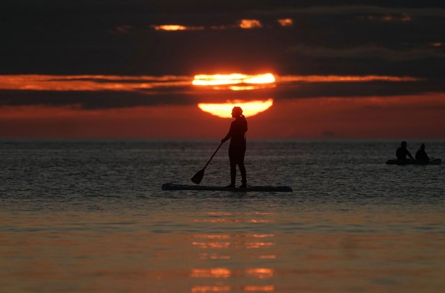 A paddleboarder watches the sunrise at Cullercoats bay in North Tyneside, England on August 8, 2020. (Photo by Owen Humphreys/PA Images via Getty Images)