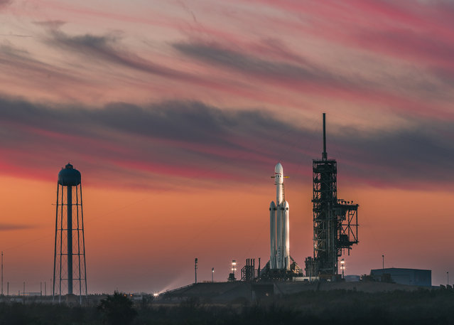 The SpaceX Falcon Heavy rocket sits on the pad at the Kennedy Space Center on February 6, 2018 ahead of its launch. The rocket weighs more than 3.1 million pounds and stands almost 230 feet high. It's designed to carry up to 140,000 pounds to low-Earth orbit, or more than 37,000 pounds all the way to Mars. (Photo by SpaceX)