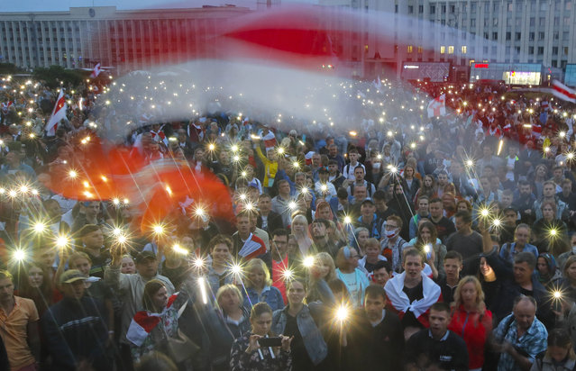 Belarusian opposition supporters light phones lights and wave an old Belarusian national flags during a protest rally in front of the government building at Independent Square in Minsk, Belarus, Wednesday, August 19, 2020. (Photo by Dmitri Lovetsky/AP Photo)