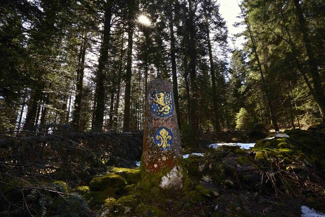 A fleur-de-lis coat of arms and the Franche Comte Lion are seen on a marker, dating from 1649, on the France (front) to Switzerland (back) border in the Marguerites Forest near Lajoux in the Vallee de Joux April 9, 2014. (Photo by Denis Balibouse/Reuters)