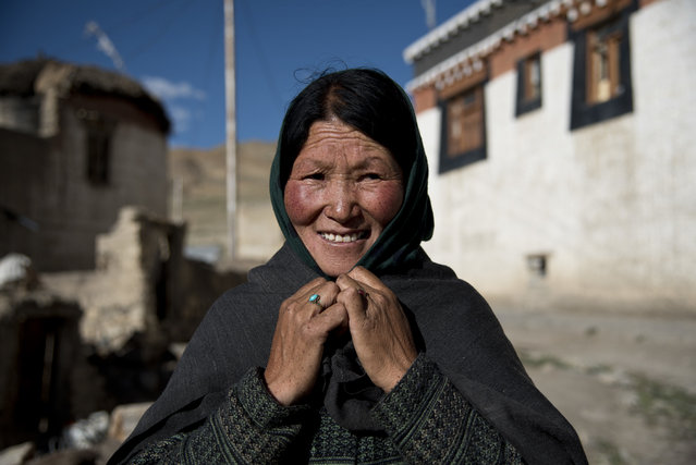 In this August 16, 2016, photo, a woman ties a scarf around her head to protect herself from the wind in the village of Kibber, in Spiti Valley, India. (Photo by Thomas Cytrynowicz/AP Photo)