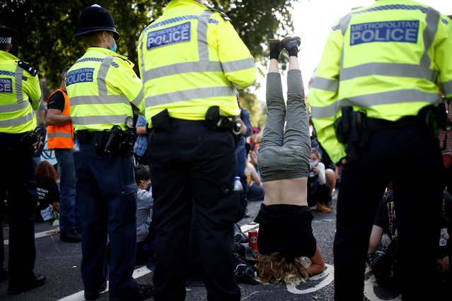 """An Extinction Rebellion climate activist stands on their head during a """"peaceful disruption"""" of British Parliament as lawmakers return from the summer recess, in London, Britain on September 1, 2020. (Photo by Henry Nicholls/Reuters)"""