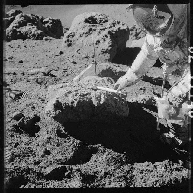 Apollo 15 commander Dave Scott takes samples at the boulder on the rim of Hadley Rille during the Apollo 15 mission in this July 1971 NASA handout photo. Astronaut James B. Irwin, lunar module pilot, can be seen in the reflection in Scott's visor. (Photo by Reuters/NASA)