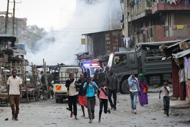Local residents run away from teargas used by riot police officers to disperse rioters during riots after an Orange Democratic Movement (ODM) rally in Nairobi, Kenya, 18 September 2016. Riots erupted after ODM supporters set on fire a pickup vehicle after the driver allegedly knocked down one of their supporter when leaving the venue of the rally. Both the Kenya's ruling party Jubilee and main opposition party ODM held their political rallies in the same constituency thus creating a tension atmosphere between the supporters as Kenyan politics starts to gear up ahead of the general election in 2017. (Photo by Daniel Irungu/EPA)