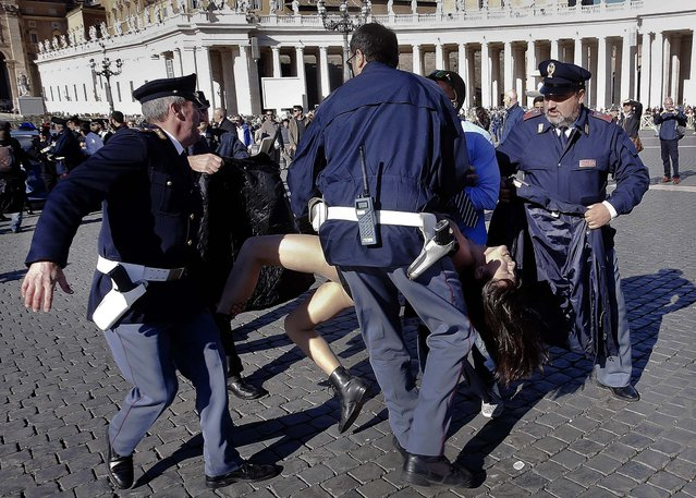 Italian police officers carry away a FEMEN activist during a protest in St. Peter's Square at the Vatican, Friday, November 14, 2014. Members of the Ukrainian feminist group Femen staged a protest against the upcoming visit of Pope Francis at the European Parliament and Council. (Photo by AP Photo)