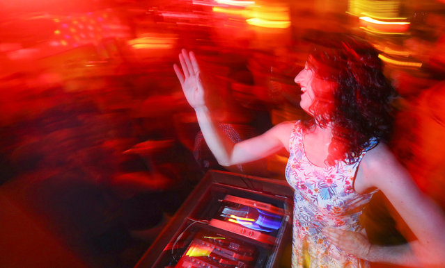 """DJ Olga Wodka performs at a party at the bar """"Zum schmutzigen Hobby"""" (""""To the dirty hobby"""") in Berlin, Germany, August 28, 2016. Celebrating pop songs and drag DJs in a little cozy place. (Photo by Hannibal Hanschke/Reuters)"""