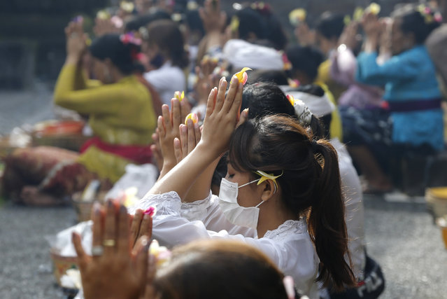 A woman wearing a face mask as a precaution against the new coronavirus outbreak during a Hindu ritual prayer at a temple in Bali, Indonesia on Wednesday, September 16, 2020. (Photo by Firdia Lisnawati/AP Photo)