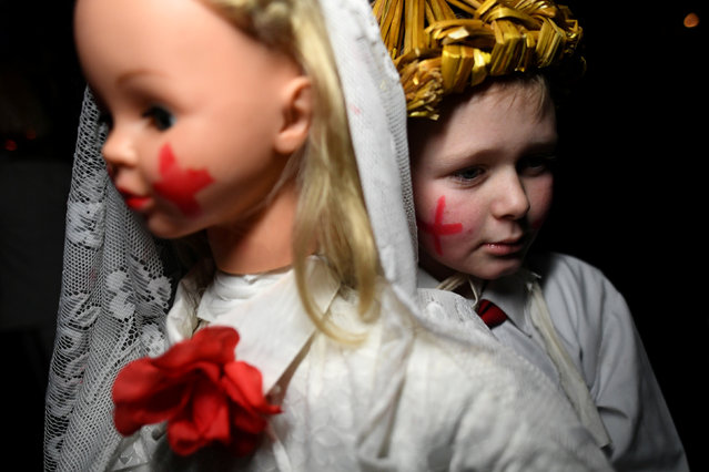 Shane Cahill, 12, carries a Brideog effigy doll before participating in a Biddy's Day parade to celebrate the Celtic festival of Imbolc, which is the arrival of springtime, in Killorglin, Ireland, February 3, 2018. (Photo by Clodagh Kilcoyne/Reuters)