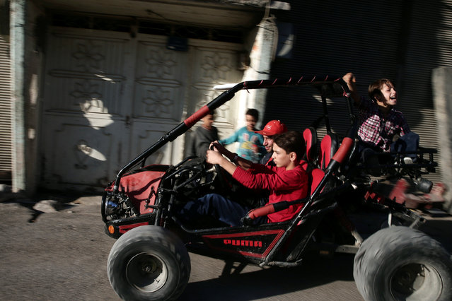 A boy drives a vehicle on the last day of Eid al-Adha celebrations in the rebel held besieged town of Hamouriyeh, eastern Ghouta, near Damascus, Syria September 15, 2016. (Photo by Bassam Khabieh/Reuters)