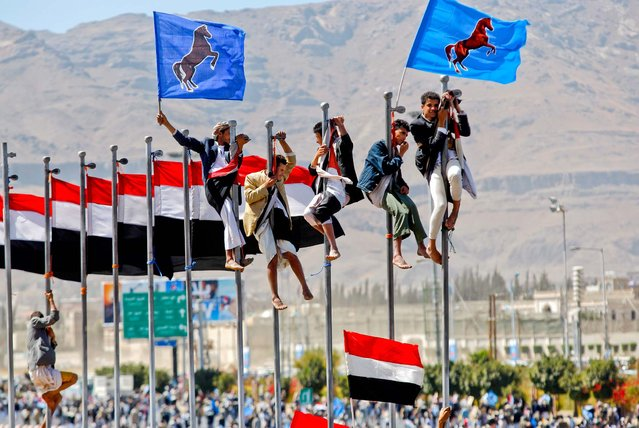 Supporters of Yemen's former President Ali Abdullah Saleh climb on flag poles during a rally marking the anniversary of his hand over of power in Sanaa, Yemen, on February 27, 2013. (Photo by Hani Mohammed/Associated Press)