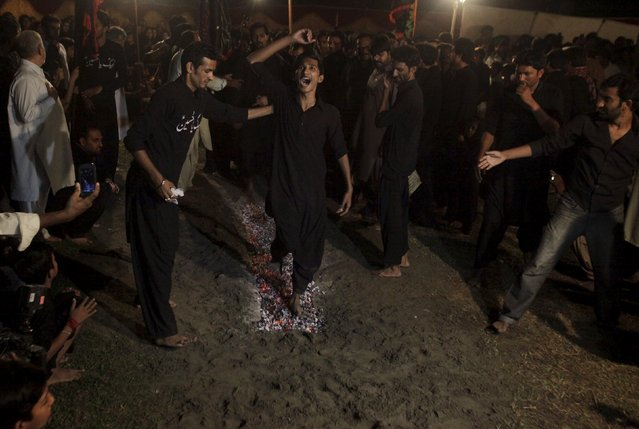 A Pakistani Shi'ite Muslim shouts religious slogans while walking on hot coals during an early morning religious gathering ahead of the Ashura festival in Lahore, Pakistan October 22, 2015. Ashura, which falls on the 10th day of the Islamic month of Muharram, commemorates the death of Imam Hussein, grandson of Prophet Mohammad, who was killed in the 7th century battle of Kerbala. (Photo by Mohsin Raza/Reuters)