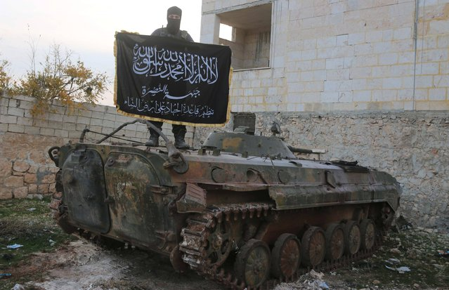 A member of al Qaeda's Nusra Front poses with the Nusra flag on top of an infantry fighting vehicle at the frontline near al-Zahra village, north of Aleppo city, November 25, 2014. Members of al Qaeda's Nusra Front and other Sunni Islamists seized an area south of the Shi'ite Muslim village in north Syria on Sunday after clashes with pro-government fighters, opposition activists said. (Photo by Abdalrhman Ismail/Reuters)