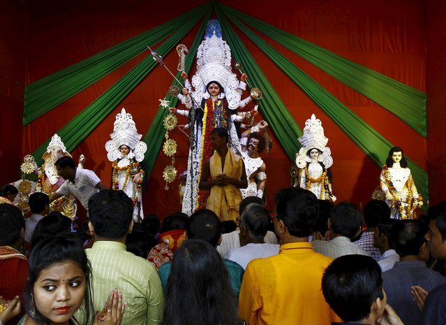 Devotees gather to worship an idol of the Hindu goddess Durga at a pandal or temporary platform during the Durga Puja festival in Kolkata, India, October 21, 2015. The Durga Puja festival is celebrated from October 19 to 22, which is the biggest religious event for Bengali Hindus. Hindus believe that the goddess Durga symbolises power and the triumph of good over evil. (Photo by Rupak De Chowdhuri/Reuters)