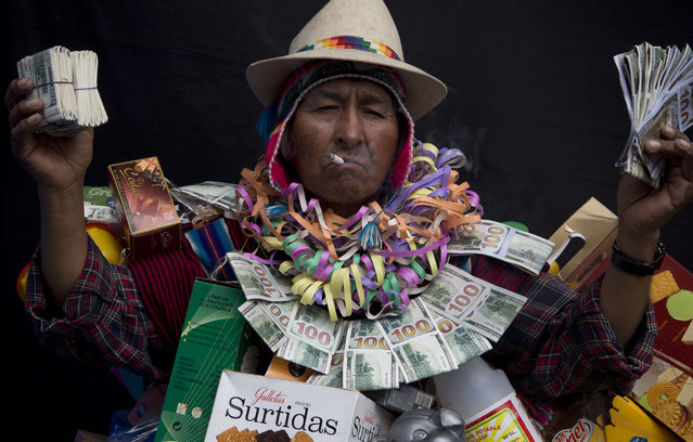 "In this February 3, 2018 photo, Alberto Macias Rios, dressed as ""Ekeko"", the god of prosperity and the central figure of the Alasita Fair, holds fake money as he poses for a portrait in La Paz, Bolivia. Macias, 65, says his low stature helps him pull off the Ekeko personality, which he's proud and happy to emulate. Macias competed in this year's Ekeko costume competition. (Photo by Juan Karita/AP Photo)"
