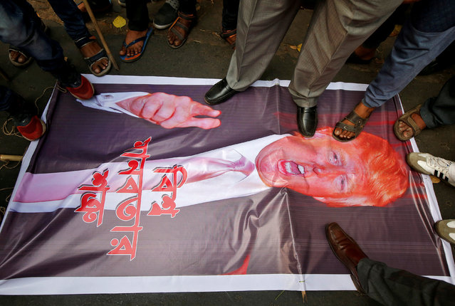 People step on a picture of U.S. President Donald Trump during a protest against what they say is bombing of civilians in Syria, outside the U.S. consulate in Kolkata, India, March 5, 2018. (Photo by Rupak De Chowdhuri/Reuters)