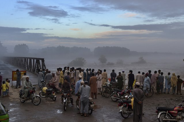 Local residents gather to watch the swallen Charsadda river flow under a bridge following heavy monsoon rainfalls, on the outskirts of Peshawar on September 2, 2020. (Photo by Abdul Majeed/AFP Photo)