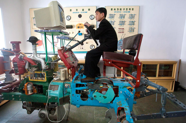 A North Korean student learns to drive a tractor on a computerized driving simulator at the Samjiyon School children's Palace in Samjiyon, North Korea, on April 3, 2012. The facility was built for children to take part in after school programs in the arts, sciences, sports, computer and vocational training. (Photo by David Guttenfelder/AP Photo)