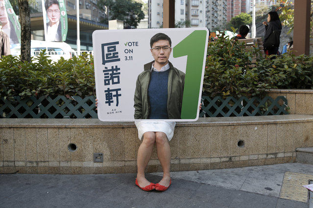 In this March 10, 2018 photo, a supporter holds a portrait of Hong Kong pro-democracy by-election candidate Au Nok-hin during an election campaign in Hong Kong. Hong Kong is holding by-elections that give opposition supporters the chance to recapture lost ground in a contest measuring residents' appetite for democracy in the semiautonomous Chinese city. Polls opened Sunday in the vote pitting pro-Beijing loyalists against opposition candidates competing for four seats in the city's semi-democratic legislature. (Photo by Kin Cheung/AP Photo)