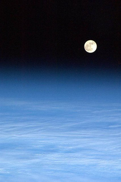 The moon rises over a light blanket of clouds in a March 4, 2013 photo taken from the International Space Station by Canadian astronaut Chris Hadfield. (Photo by Chris Hadfield/CSA via AFP Photo)
