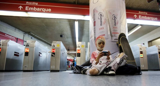 "A reveller plays with his mobile phone at a metro station before he attends the ""Zombie Walk"" parade in Sao Paulo, Brazil, November 2, 2015. (Photo by Paulo Whitaker/Reuters)"