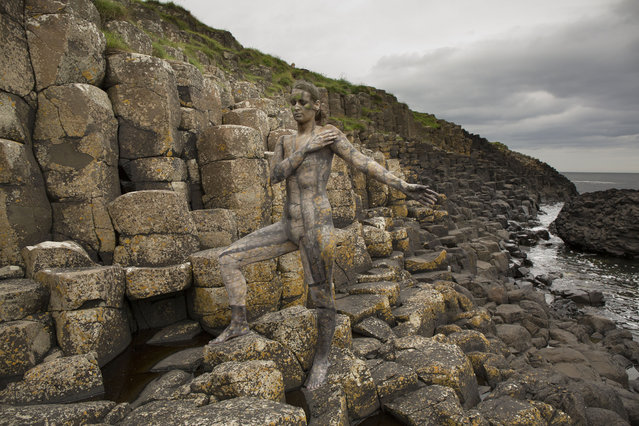 A woman becomes one with nature and history at UNESCO World Heritage site Giants Causeway in Buhmills, UK. (Photo by Trina Merry/Caters News)