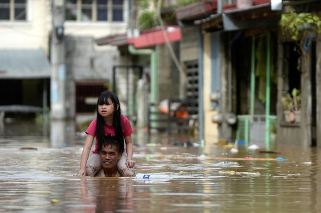 A man carrying a child on his shoulders wades through a flooded street following Typhoon Vamco, in Rizal Province, Philippines, November 12, 2020. (Photo by Lisa Marie David/Reuters)
