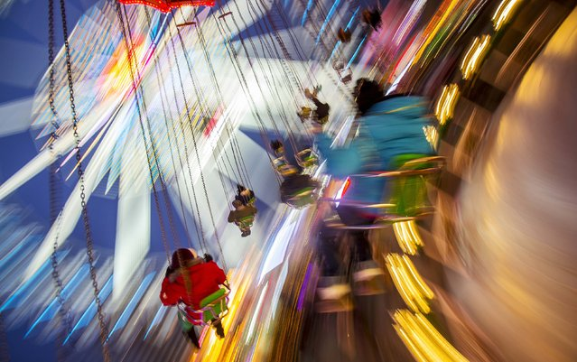 Children ride on a merry-go-round at a Christmas market in Berlin November 29, 2014. (Photo by Hannibal Hanschke/Reuters)
