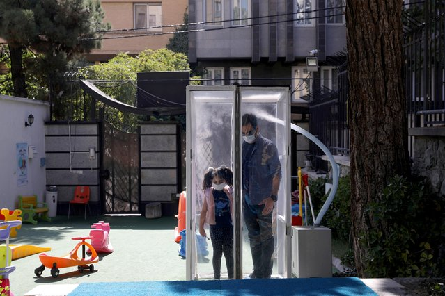 An Iranian man and his daughter get disinfected before they enter the kindergarten, in Tehran, Iran, October 19, 2020. (Photo by Majid Asgaripour/WANA)