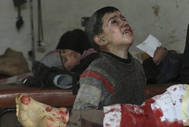 Injured children wait for treatment in a field hospital after what activists said was an air strike by forces loyal to Syria's President Bashar al-Assad in the Duma neighbourhood of Damascus December 23, 2014. (Photo by Mohmad Badra/Reuters)